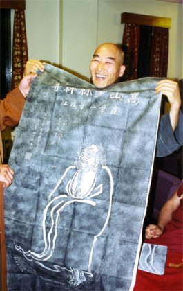 Jisu Sunim holding up a rubbing of Bodhidharma which has just been presented to him by Shi Yanzi. Photo © Gerda Chapuis