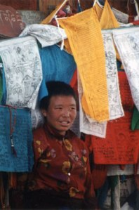 Girl with Tibetan prayer flags. Photo: © Lisa Daix