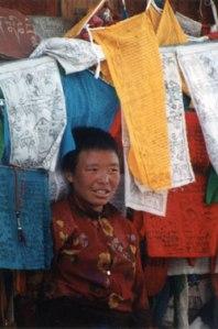Girl with Tibetan prayer flags. Photo: © Lisa Daix