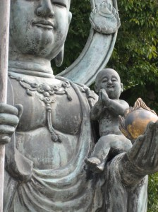 A baby perches on Jizo's arm at Taizo-in, the oldest sub-temple of Myoshin-ji. Photo © @KyotoDailyPhoto