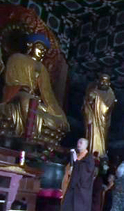 Chinese monk walking passed Buddha rupa. Possibly a statue of bodhidharma on right.