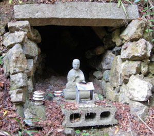 A statue of Kobo Daishi (774–835) guards a tiny hollow at Sankaku-ji representing the cave at Cape Muroto